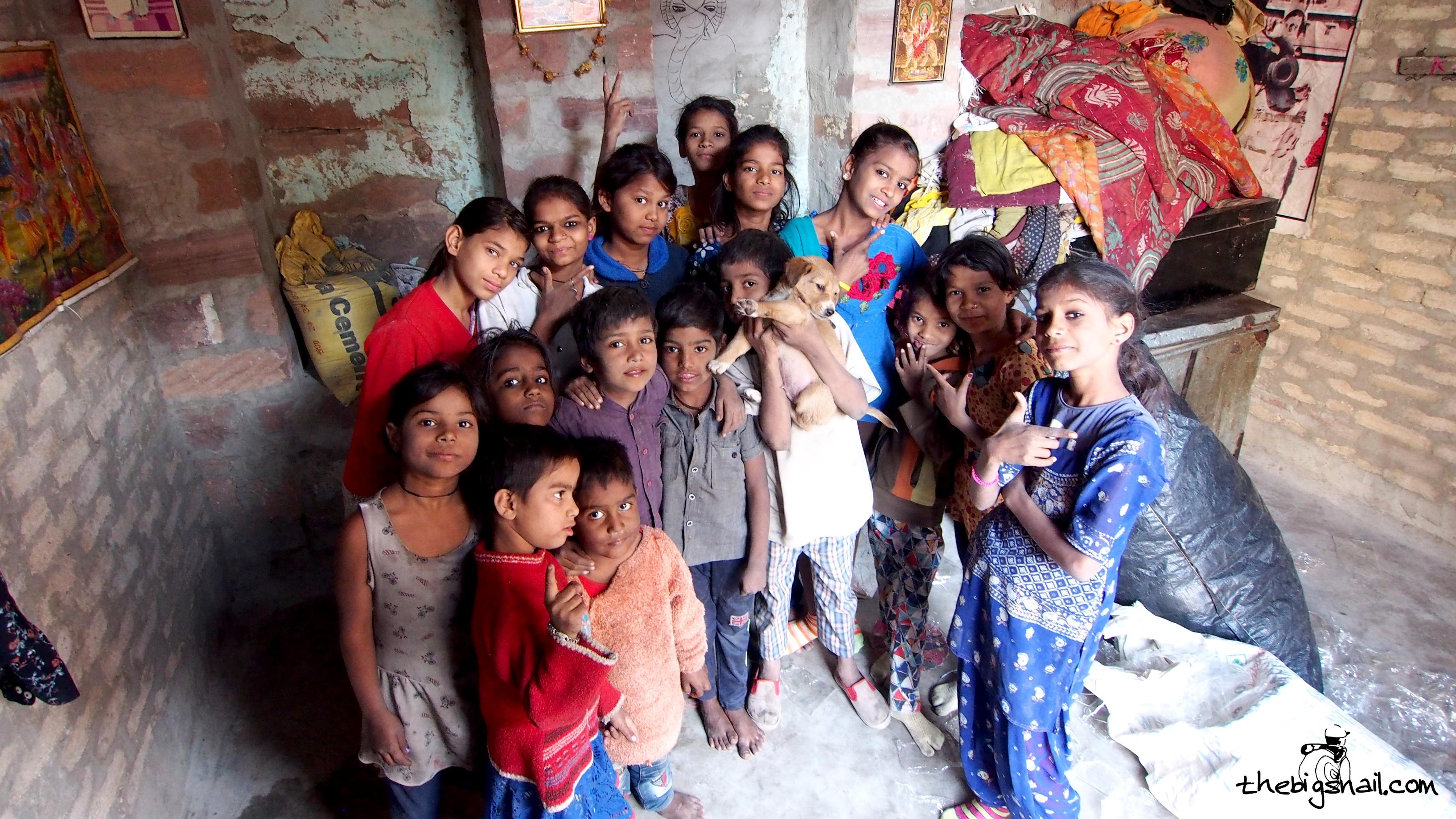 Anjali avec une dizaine de ses sœurs et quatre garçons dans une petite pièce aux murs de brique.