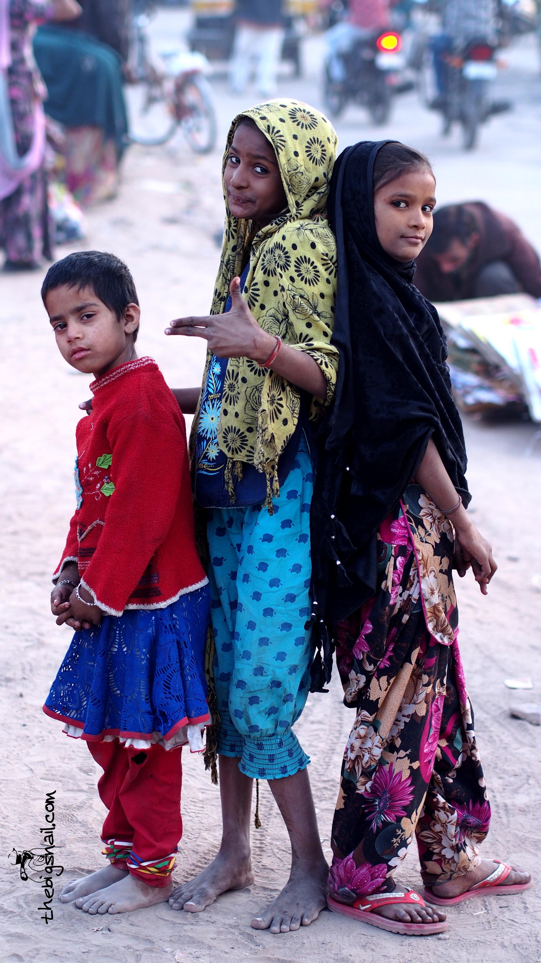 Trois fillettes dont deux pieds nus dans la poussière du marché de Ghanta Ghar